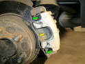 Left and Right Sides - Remove the retaining spring (yellow arrow) on the front of the brake caliper.