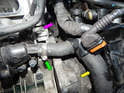 After draining the coolant from the engine, loosen and remove the hose clamp (green arrow) holding the hose to the thermostat housing.