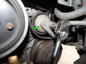 Rotate the belt tensioner clockwise to release tension on the belt and slide it off the crankshaft, tensioner and AC compressor pulley.