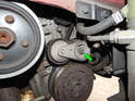 Loosen and remove the 13mm bolt (green arrow) holding the out belt tensioner to the engine.