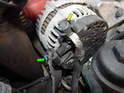 Press the tab on the electrical connector (green arrow) leading to the alternator and pull it off.