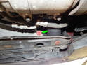Locate the radiator drain plug on the right side near the bottom of the radiator (green arrow).