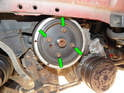 Next loosen and remove the four 13mm bolts (green arrows) from the pulley.