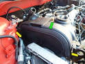 Now move up to above the engine and carefully remove the front plastic cover (green arrow).