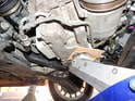 You'll now want to place a floor jack with a block of wood or cardboard under the oil pan as shown here.