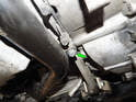 Loosen and remove the 10mm bolt (green arrow) holding the rear of the intake tube to the oil pan.