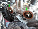 Note the camshaft seals behind the VVT units (green arrows).