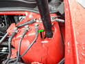 Carefully pry the hood shock off the lower ball pivot by using a large screwdriver behind the attachment point (green arrow).