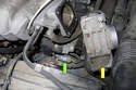 With the throttle housing (yellow arrow) placed aside, you can now disconnect the electrical connector (green arrow).