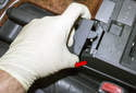 Working at the parking brake handle trim, pull the top of the trim off toward the left, and then out (red arrow).