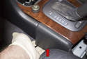 Working at the left side of the center console, pull the lower corner away from the center tunnel (red arrow).