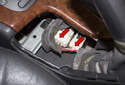 Working below the parking brake handle, unplug the two electrical connectors (red arrows).