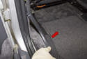 Rear trim: Working at the B-pillar, detach the trim piece by pushing it toward the center of the vehicle (red arrow).