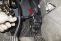 Using a trim panel tool, detach the wiring harness mount from the sensor (red arrow).