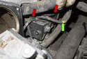 Working at the lower front corner of the cylinder head, near the throttle housing mounting bore, remove the camshaft wiring harness (green arrow) from the plastic mounts (red arrows).