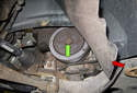 Open the plastic access cover (red arrow) to gain access to the crankshaft pulley (green arrow).