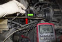 In this photo the wrench (red arrow) is close to the sensor (green arrow), so the DVOM reads 5 volts.