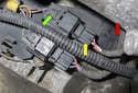Working beneath the intake manifold, locate the crankshaft sensor electrical connector (green arrow).