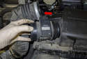 Remove the mass air flow sensor by pulling it straight out of the intake air housing (red arrow).