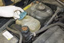 Working in the engine compartment, remove the expansion tank cap green arrow).