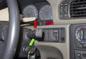 Continue to hold the trip reset button (red arrow) and turn the ignition ON (green arrow).