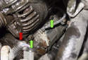 Working below the alternator (red arrow), remove the two 12mm A/C compressor fasteners (green arrows).