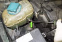Working at the bottom of the coolant expansion tank, using a flathead screwdriver, loosen the hose clamp (green arrow).