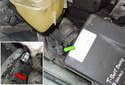Working between the coolant expansion tank and the E-box, disconnect the electrical connector (green arrow) by pressing the release tab (red arrow) and pulling it apart.
