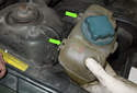 Lift the expansion tank up to detach it from the mounts (green arrow).