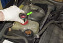 Once the coolant level is lowered, install the pressure tester adapter (green arrow) to the coolant expansion tank.