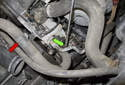 Working at the power steering pump, use a flathead screwdriver and loosen the hose clamp (green arrow).