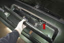 Pull the tail gate handle out of the tail gate, feeding the wire through the hole (red arrow).
