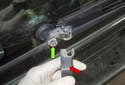 Working at the wiper arm pivot, remove the plastic cap (red arrow) by opening it and pulling it off.