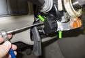 Using a long T20 Torx bit, remove the two ignition switch screws (green arrows).