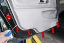 Using a door panel clip tool, release the door panel clips (red arrows).