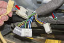 Then, disconnect the power mirror electrical connectors, by pressing the release tab (red arrow) and pulling the connector straight out.