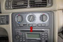 The climate control panel is located in the center dashboard (red arrow).