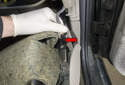 Glove box: Disconnect the footwell light electrical connector (red arrow) by pulling it straight off the light.