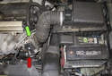 The engine starter motor (red arrow) is located on front of the engine below the intake manifold (green arrow).