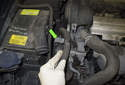 Then pull the power steering hose out of the mounting bracket (green arrow) and place it aside.