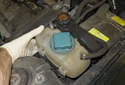 Unclip and slightly lift the coolant and power steering reservoirs.
