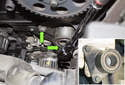 Locate the idler pulley, remove the two 13mm fasteners (green arrows) and remove the idler pulley from the engine.