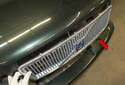 Once the clips are removed, slide the grille out of the hood to remove it (red arrow).