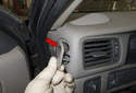 Working at the left corner of the dashboard, remove the air duct (red arrow).