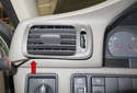 Working at the left corner of the dashboard, remove the air vent (red arrow).