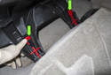 Rear Seat: With the seat cushion folded forward, press the release levers to unlock the seat cushion bracket (red arrow).