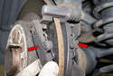 Remove the brake pads (red arrows) from the caliper bracket.