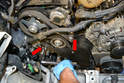 You can now remove the last two T30 Torx screws holding the lower timing belt cover on (red arrows).