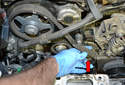 Slip the belt off the coolant pump first (red arrow).