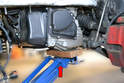 Left Side- Use a piece of wood to help spread the load and place a floor jack under the transmission (red arrow).